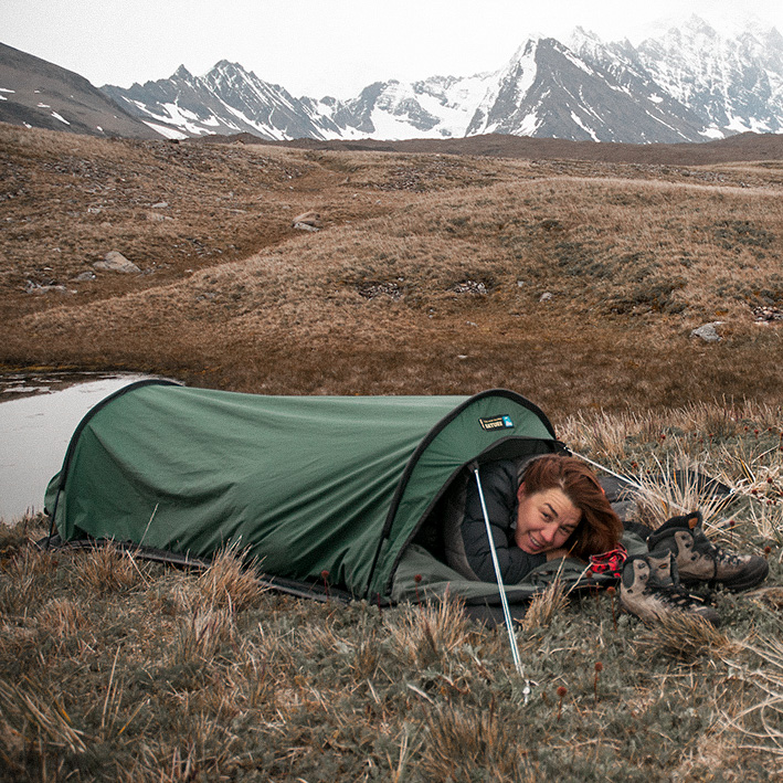 A woman (Justine Shaw) poking her head out of a tent, with mountains in the background