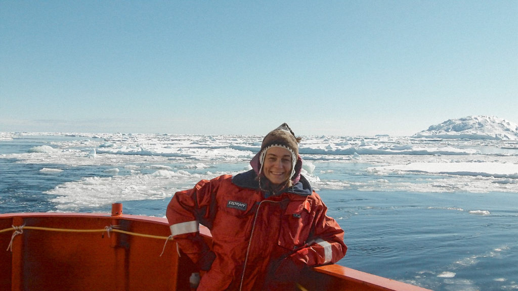 A woman (Leanne Armand) stood at the prow of a ship in front of some iceburgs