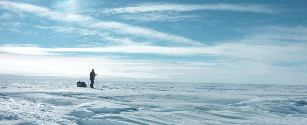 A figure pulling a sled across a snow-covered landscape