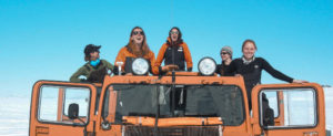 5 women standing on a yellow truck in an ice field